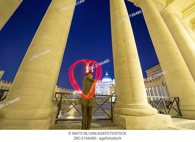 Woman light painting a heart in Vatican City In Rome, Italy