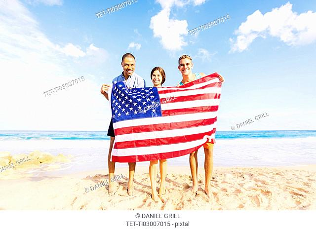 Young people holding American flag on beach