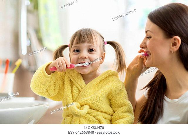 5424df19e7 Beautiful mother and kid daughter brushing teeth in bathroom