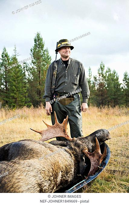 Smiling man with dead elk at hunting