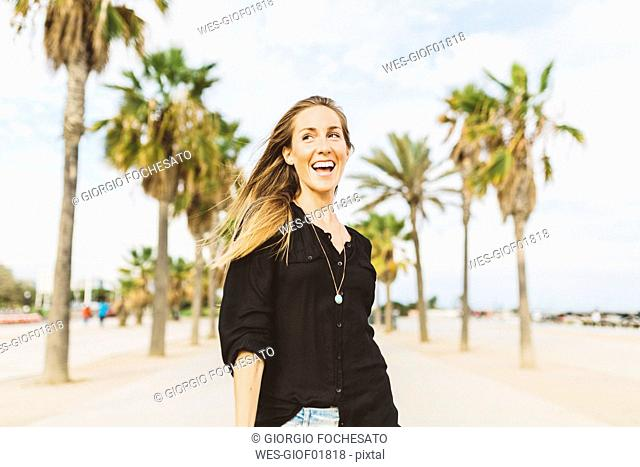 Happy young woman on waterfront promenade
