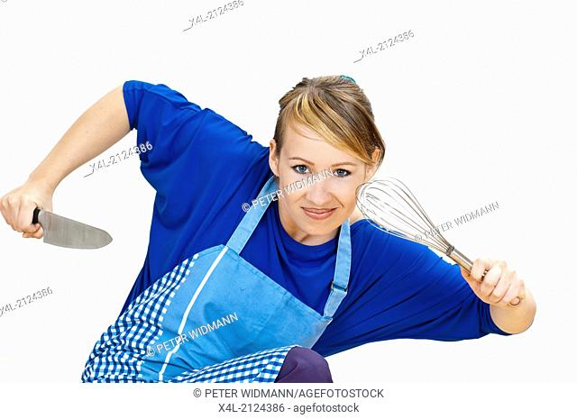 housewife with knife and cooking whisk in position for attack (model-released)