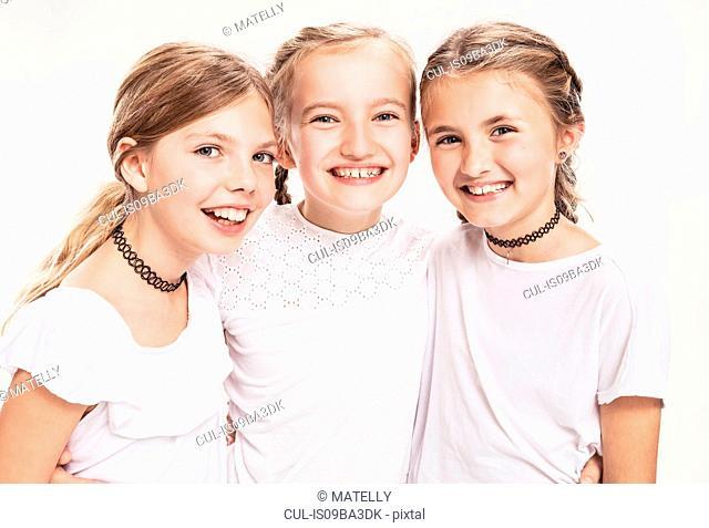 Studio portrait of three girls with blond hair, waist up