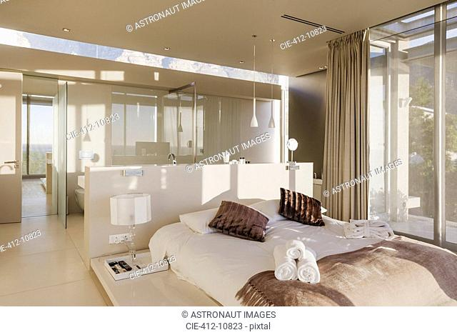 Bed and bathroom in modern master bedroom