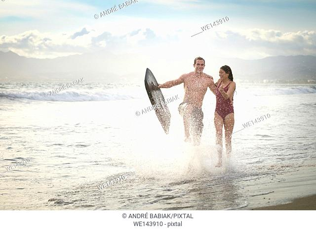 Young couple running at the beach with boogie board, splashing water. Riviera Nayarit, Mexico