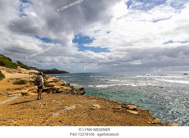 A hiker stands on a cliff watching an approaching rain storm; Poipu, Kauai, Hawaii, United States of America