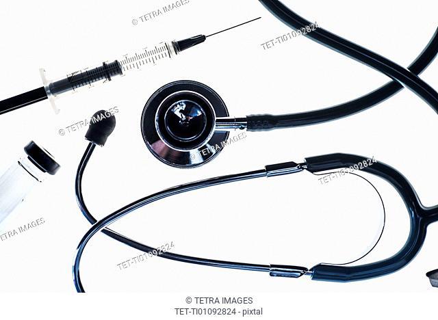 Stethoscope, syringe and test tube on white background
