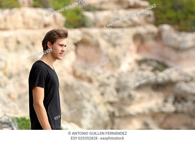 Portrait of a man exploring and looking away in the mountain with an unfocused background