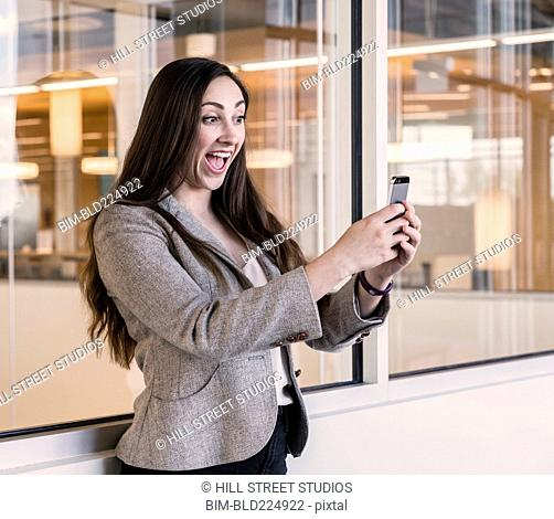 Businesswoman taking selfie with cell phone in office