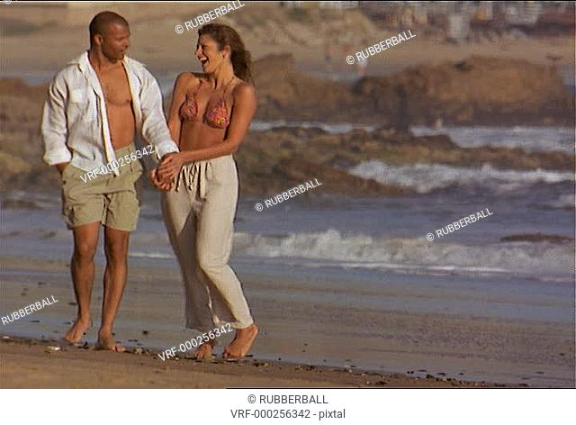 wide shot as an attractive couple walk holding hands and talking as they stroll up the beach