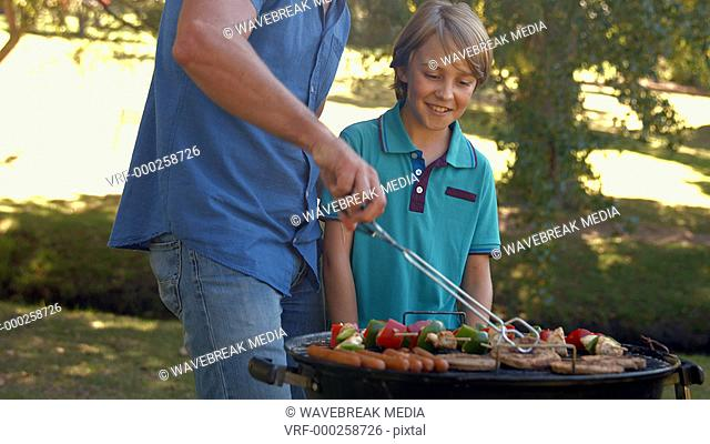 Happy father doing barbecue with his son