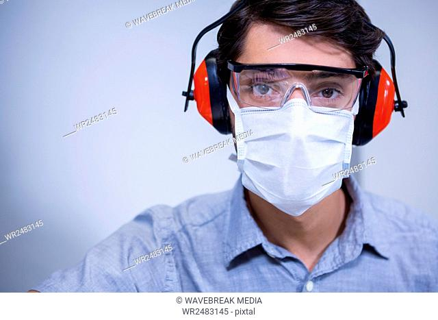 Dentist in protective glasses and headphones