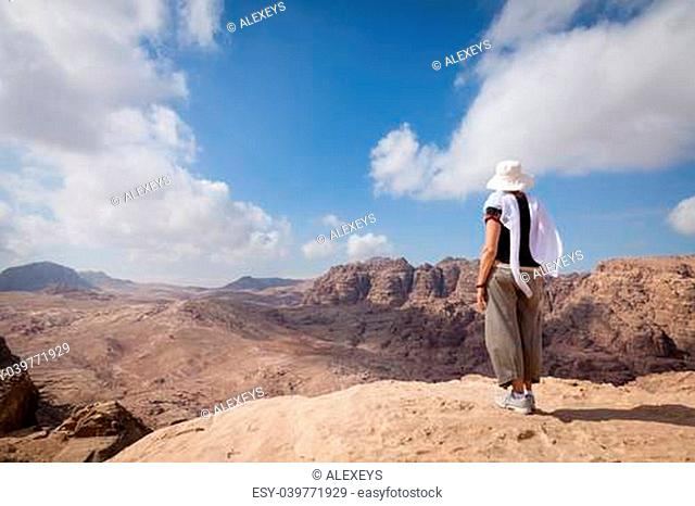 Woman is admiring a view of Jordanian desert while hiking in Petra