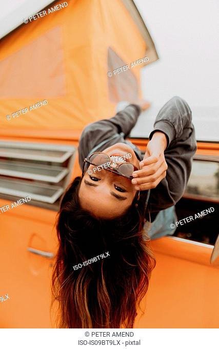 Young woman hanging out of recreational vehicle window at beach, portrait, Jalama, California, USA