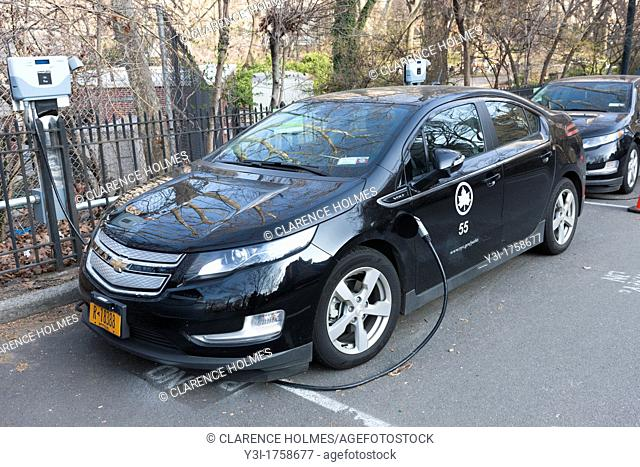 A Chevy Volt plug-in hybrid electric vehicle, used by the New York City Parks and Recreation department, receives a charge at a charging station in Central Park