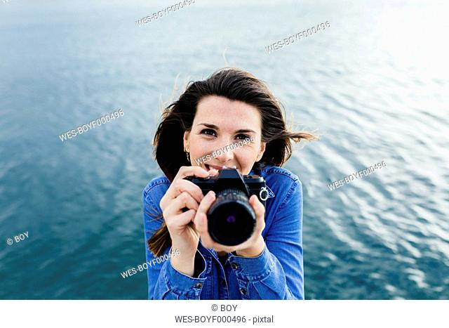Smiling young woman at the waterfront holding camera