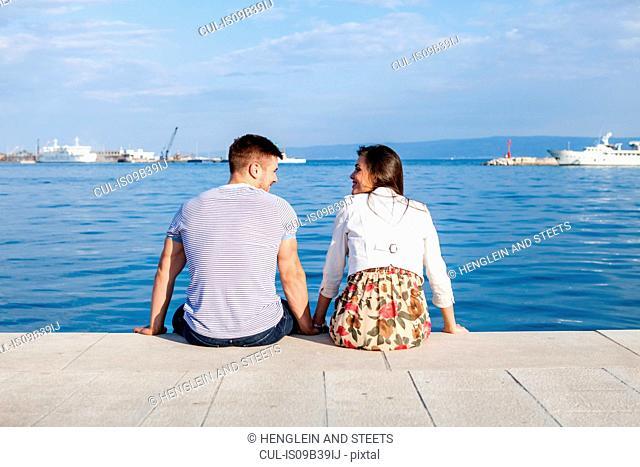 Rear view of couple sitting on harbour, Split, Dalmatia, Croatia