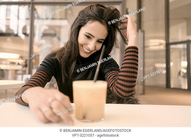 portrait of happy woman with healthy juice glass enjoying break at table in café, playing with hairs, candid emotional, unposed, in Munich, Germany