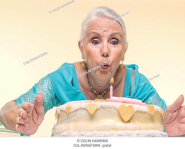 Studio portrait of senior woman blowing out birthday candle