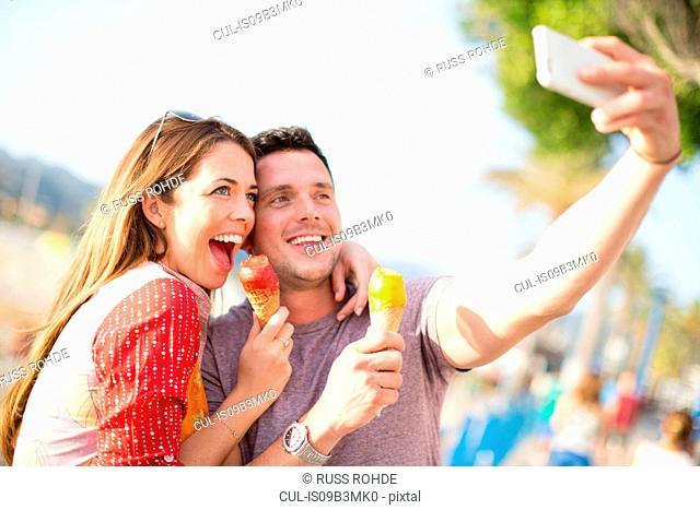 Couple taking selfie eating ice cream cones, Majorca, Spain
