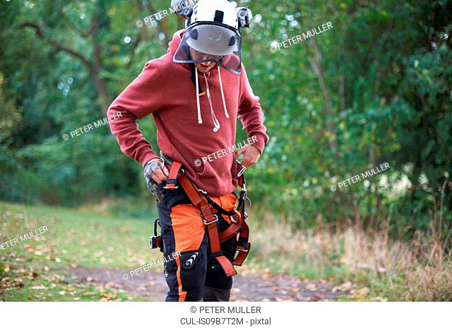 Young male trainee tree surgeon fastening safety harness