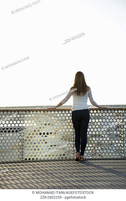 Rear view of a young woman standing by the fence outdoors