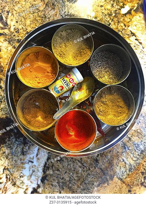 Colorful combination of seven essential spices used in North Indian cooking in a round container on a granite counter