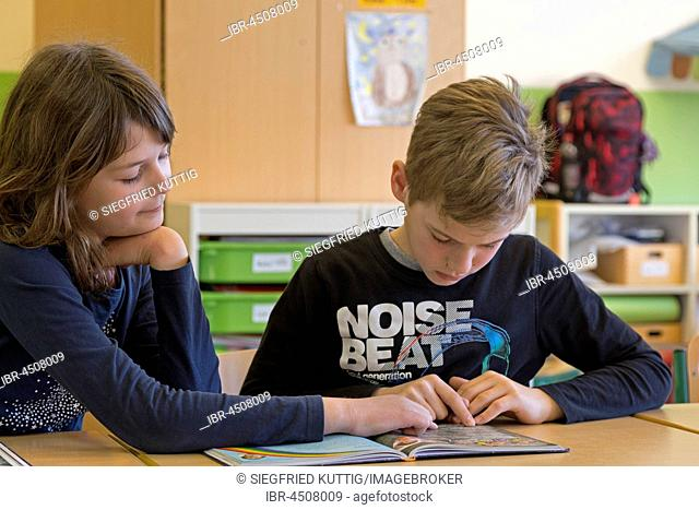 Students, children reading a book together, classroom, elementary school, Lower Saxony, Germany