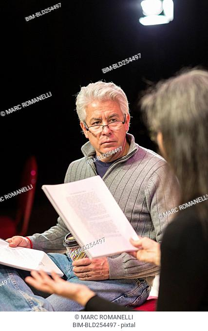 Hispanic man and woman reading scripts in theater