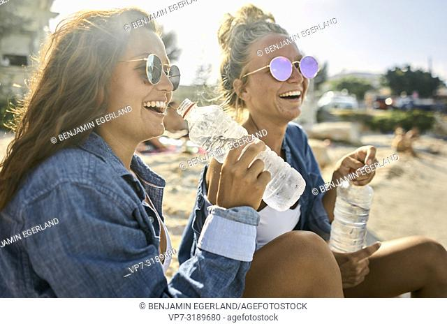 Two women sitting at beach, Chersonissos, Crete, Greece