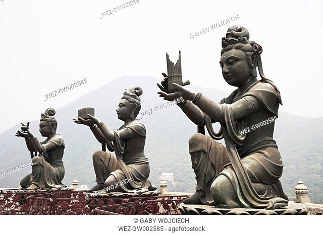 China, Hongkong, Lantau Island, Ngong Ping, three buddhistic statues praising, making offerings to Tian Tan Buddha