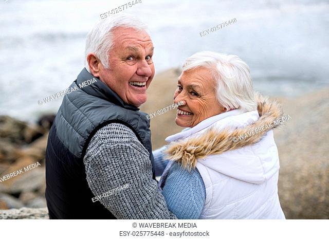 Portrait of senior couple sitting on rock at beach