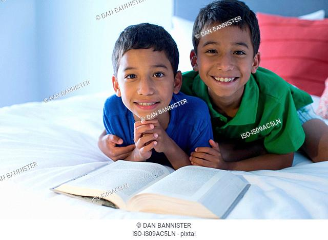 Brothers looking up from book on bed