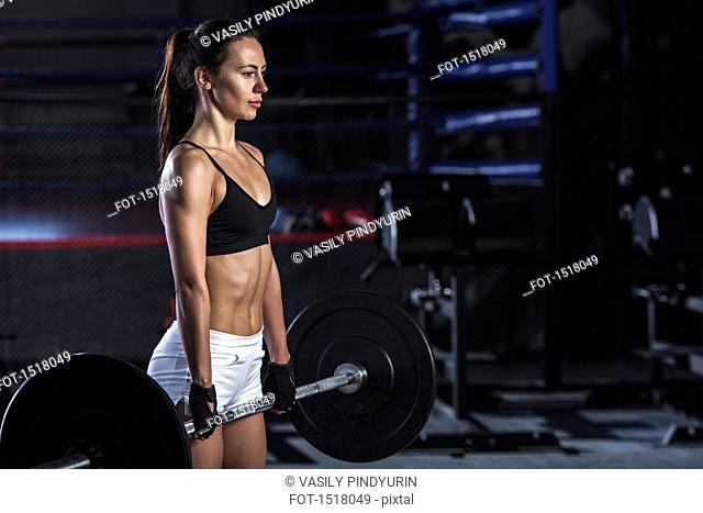 Young female athlete picking up barbell at gym