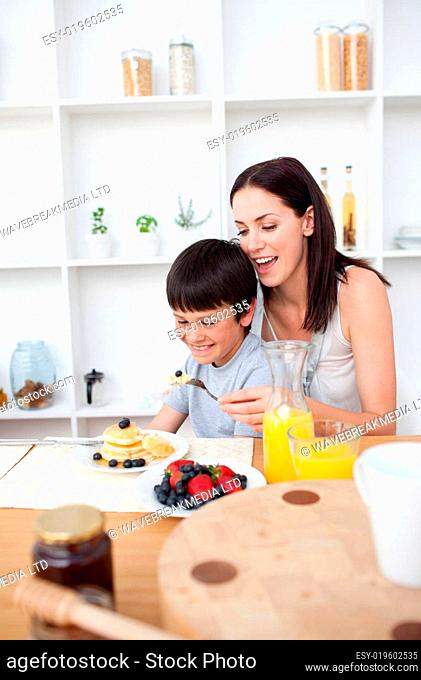 Smiling boy eating pancakes with his mother for breakfast