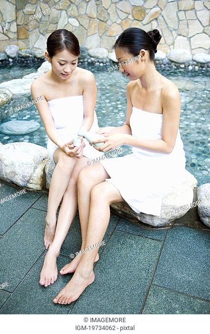Two naked young women with towel sitting by pool, talking