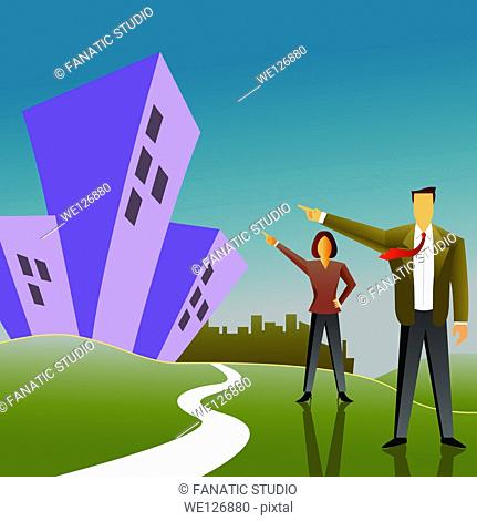 Businessman with a businesswoman pointing towards apartments