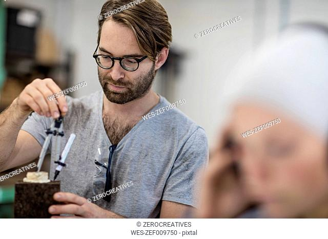 Man using compasses on object