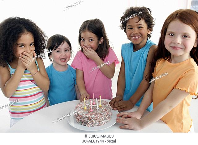 Group of children smiling around birthday cake indoors