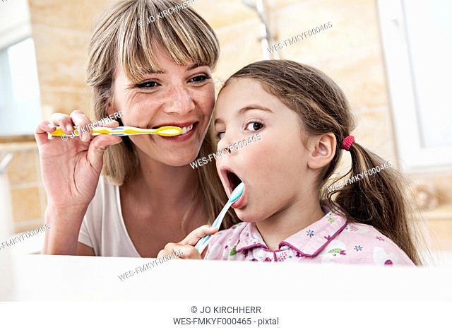 Germany, North Rhine Westphalia, Cologne, Mother and daughter brushing teeth in bathroom