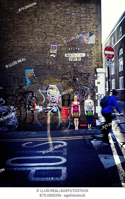 Un ciclista irreconocible circulando por una calle y en la pared de fondo pintada con graffitis. Buxton St. East End, London, UK, Europa