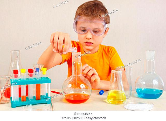 Young cute boy in safety goggles is engaged in chemical experiments in the laboratory