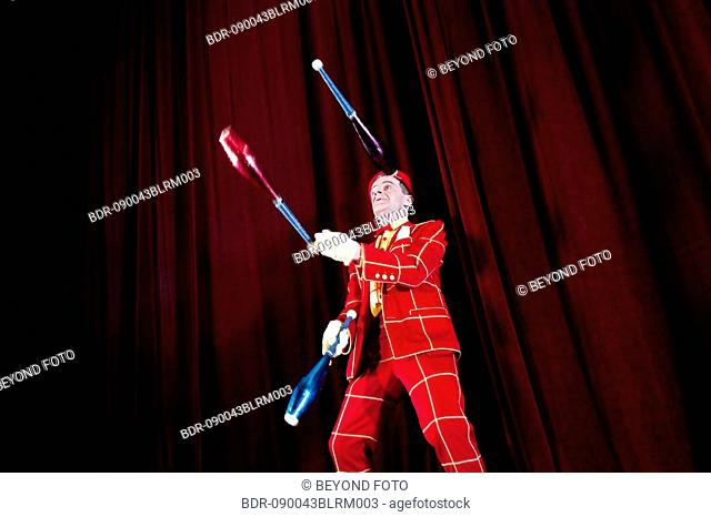 clown on stage performing with juggling clubs