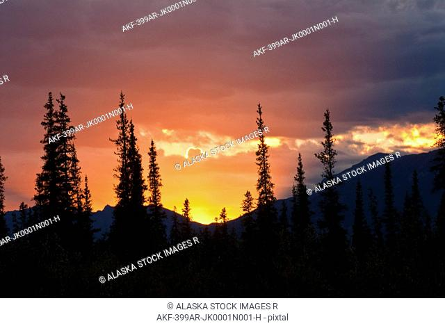 Shafts of light peek through the clouds at sunset near the Alatna River in Gates of the Arctic National Park and Preserve, Arctic Alaska, Summer
