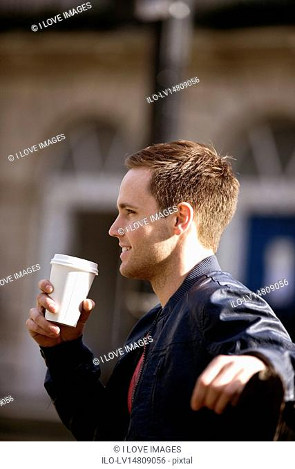 A young man sitting on a bench, holding a paper cup