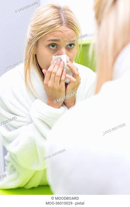 Young woman blowing nose in tissue paper while looking at mirror