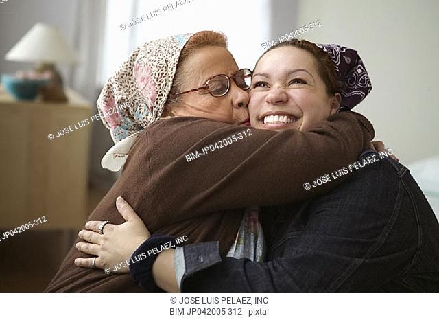 Elderly woman kissing daughter