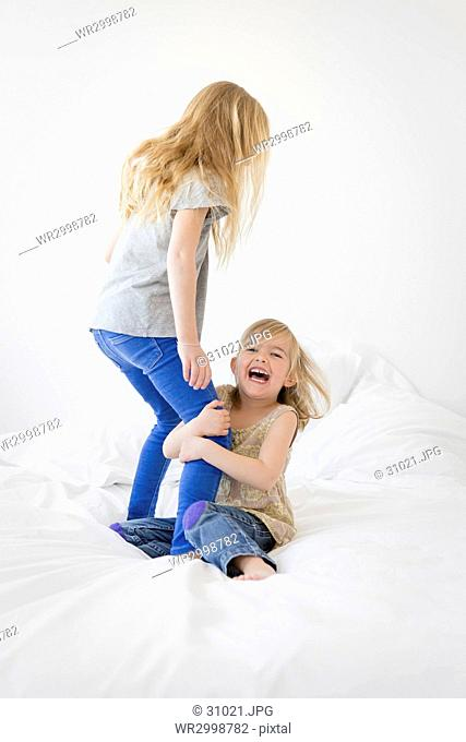 Two blond girls on a bed, younger girl sitting, holding on to legs of older girl standing