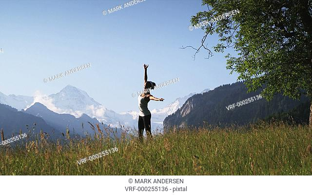 woman stretching and exercising in a mountain field