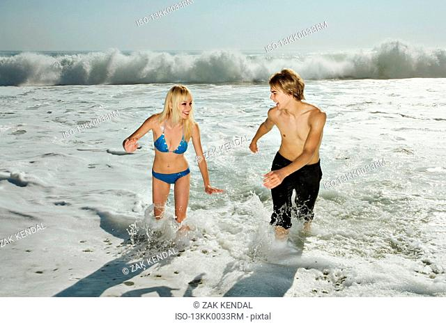 Couple, laughing, running from waves